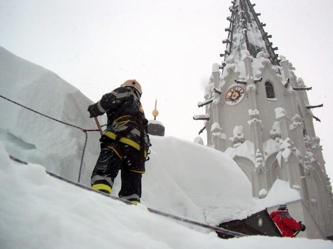 Ein Feuerwehrler steht gesichert durch Seile am Dach der Basilika Mariazell