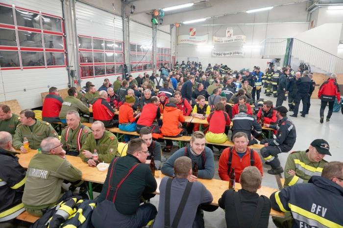 Alle Einsatzkräfte sitzen zusammen in der Fahrzeughalle