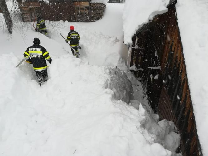 Einsatzkräfte schaufeln auf einem rießen Schneeberg vor einem Haus